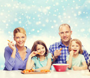 Happy family with two kids making dinner at home. Food, family, children, happiness and people concept - happy family with two kids making dinner over blue sky Stock Images