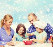 Happy family with two kids making salad at home Stock Photo
