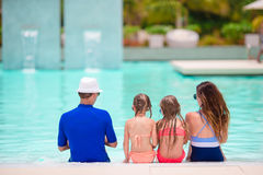 Happy family with two kids in outdoor swimming pool. Happy family enjoying bath time in infinity pool Royalty Free Stock Photography