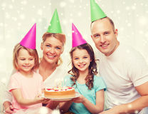 Happy family with two kids in party hats at home Stock Image