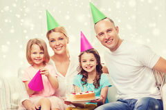 Happy family with two kids in party hats at home Stock Images
