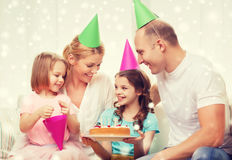 Happy family with two kids in party hats at home Royalty Free Stock Photography