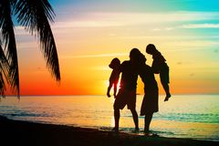 Happy family with two kids play on sunset beach. Happy family with two kids play on sunset tropical beach Royalty Free Stock Photos
