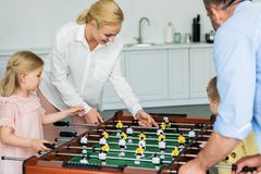 happy family with two kids playing table football together royalty free stock images