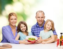 Happy family with two kids with salad at home Stock Images