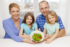 Happy family with two kids with salad at home Stock Photo