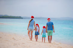 Happy family with two kids in Santa Hats on summer vacation. Christmas holidays with young family of four enjoying their Stock Image
