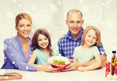 Happy family with two kids showing salad in bowl Royalty Free Stock Image