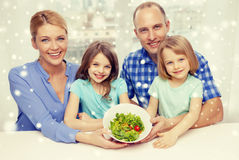 Happy family with two kids showing salad in bowl Royalty Free Stock Images