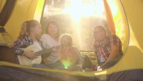 Happy family with two kids sitting in tent and enjoying guitar stock footage