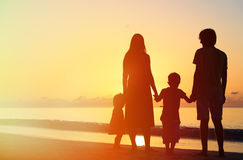 Happy family with two kids on sunset beach Stock Photo
