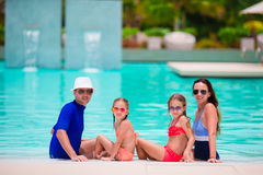 Happy family with two kids in swimming pool. Smiling parents and children on summer vacation swim and having fun. Royalty Free Stock Photos