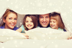 Happy family with two kids under blanket at home Stock Photo