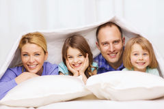 Happy family with two kids under blanket at home Royalty Free Stock Photos