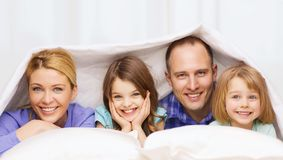 Happy family with two kids under blanket at home Royalty Free Stock Photo