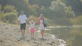 Happy family with two kids walking along the shore stock video footage