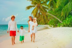 Happy family with two kids walking on beach. Happy family with two kids walking on tropical beach Royalty Free Stock Images