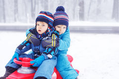 Happy family: two little twin boys having fun with snow in winte Stock Images