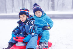 Happy family: two little twin boys having fun with snow in winte Stock Photography
