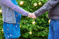 Happy family of two outdoors at Christmas. Beautiful expecting couple, husband and his pregnant wife, near decorated Christmas tree Royalty Free Stock Image