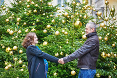 Happy family of two outdoors at Christmas. Beautiful expecting couple, husband and his pregnant wife, near decorated Christmas tree Stock Photo