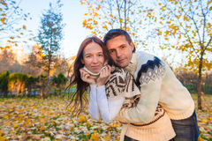 Happy family of two walking in autumn park on a Stock Photos