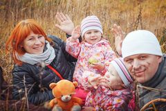 Happy family with two 1 year old girls have rest in a yellow field stock photo