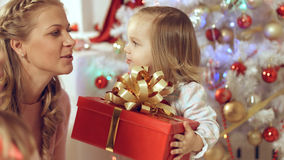 Happy family with two young daughters at the Christmas tree with gifts Royalty Free Stock Photo