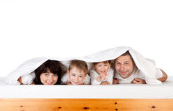 Happy family under blanket. Happy family looking out from blanket or duvet under bed; white studio background Stock Photography