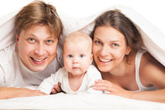 Happy family under blanket on the bed at home Royalty Free Stock Photography