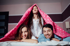 Happy family under a blanket Royalty Free Stock Images