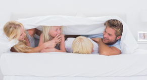 Happy family under the duvet playing Royalty Free Stock Photos