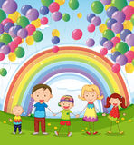 A happy family under the floating balloons with a rainbow Royalty Free Stock Images