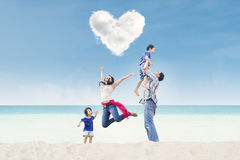 Happy family under heart cloud at beach. Happy family jumping under heart cloud at the beach Stock Photography