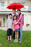 Happy family under one umbrella outside their home Stock Photos