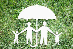 Happy family under protection on backdrop of green grass Stock Image