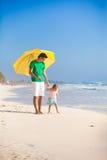 Happy family under yellow umbrella on white sandy Royalty Free Stock Image