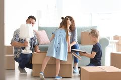 Happy family unpacking box indoors. Moving into new house royalty free stock photos