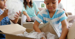 Happy family unpacking cardboard boxes. At home stock footage