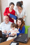 Happy  family uses  various electronic devices in home Royalty Free Stock Image