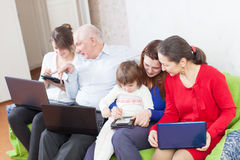 Happy  family uses  various portable computers in home Stock Photos