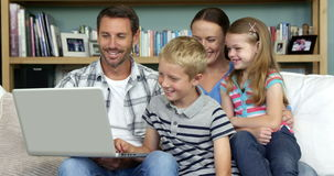 A happy family is using a computer. In the lounge stock footage