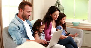 Happy family using devices on sofa stock video footage