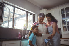 Happy family using digital tablet in kitchen Stock Photo