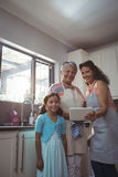 Happy family using digital tablet in kitchen Stock Images