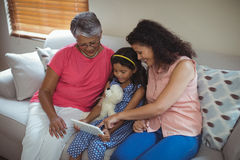 Happy family using digital tablet in living room Stock Photos