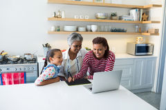 Happy family using graphic tablet while looking at laptop in kitchen Stock Photo