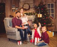 Happy family using hexacopter drone. Happy family sitting with gift boxes and using hexacopter drone royalty free stock image