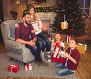 Happy family using hexacopter drone. Happy family sitting with gift boxes and using hexacopter drone royalty free stock photo