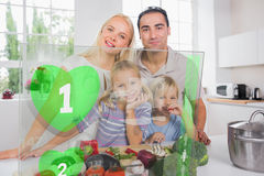 Happy family using interface to prepare dinner Royalty Free Stock Images